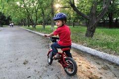 Um menino branco pequeno da criança que veste um capacete protetor no seu ele Imagens de Stock