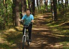 Um menino caucasiano novo est? montando a bicicleta em um dia ensolarado imagens de stock