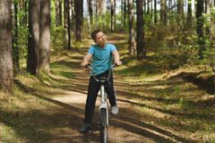 Um menino caucasiano novo est? montando a bicicleta em um dia ensolarado fotos de stock royalty free