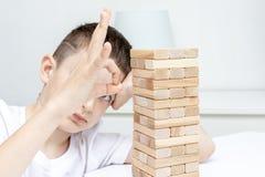 Um menino caucasiano preteen furado que tenta jogar o jogo de mesa de madeira da torre do bloco para manter-se distraído fotos de stock