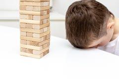 Um menino caucasiano preteen furado que tenta jogar o jogo de mesa de madeira da torre do bloco para manter-se distra?do fotos de stock