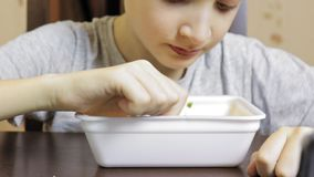 Um menino caucasiano preteen que come o fast food chineese, macarronetes imediatos do recipiente descartável em casa, sua boca es video estoque