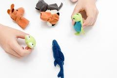 Um menino caucasiano que joga fantoches do dedo, brinquedos, bonecas - as figuras dos animais, heróis do teatro do fantoche puser foto de stock