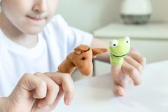 Um menino caucasiano que joga fantoches do dedo, brinquedos, bonecas - as figuras dos animais, her?is do teatro do fantoche puser imagem de stock royalty free