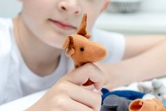 Um menino caucasiano que joga fantoches do dedo, brinquedos, bonecas - as figuras dos animais, her?is do teatro do fantoche puser foto de stock
