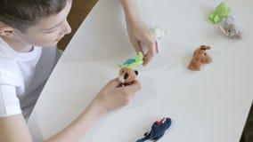 Um menino caucasiano que joga fantoches do dedo, brinquedos, bonecas - as figuras dos animais, her?is do teatro do fantoche puser vídeos de arquivo