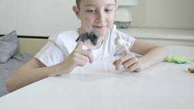 Um menino caucasiano que joga fantoches do dedo, brinquedos, bonecas - as figuras dos animais, her?is do teatro do fantoche puser video estoque