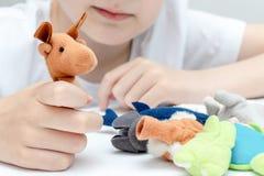 Um menino caucasiano que joga papéis diferentes usando fantoches do dedo, brinquedos para expressar suas emoções, agressão, medo  fotografia de stock royalty free