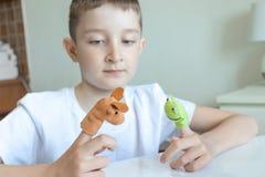 Um menino caucasiano que joga pap?is diferentes usando fantoches do dedo, brinquedos para expressar suas emo??es, agress?o, medo  foto de stock royalty free