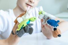 Um menino caucasiano que joga pap?is diferentes usando fantoches do dedo, brinquedos para expressar suas emo??es, agress?o, medo  imagem de stock