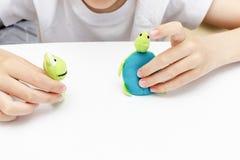 Um menino caucasiano que joga pap?is diferentes usando fantoches do dedo, brinquedos para expressar suas emo??es, agress?o, medo  fotografia de stock