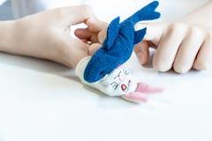 Um menino caucasiano que joga pap?is diferentes usando fantoches do dedo, brinquedos para expressar suas emo??es, agress?o, medo  fotos de stock royalty free