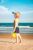 Um menino com balde e pá de pedreiro na praia que olha o horizonte Fotos de Stock