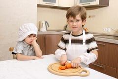 Um menino com cenoura e faca Fotos de Stock
