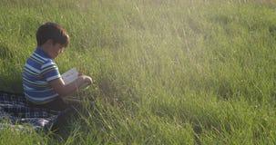 Um menino com um livro senta-se no meio de um gramado verde na noite filme