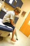 Um menino com muletas senta-se, esperando o doutor fotos de stock