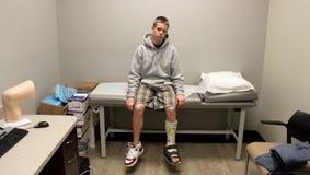 Um menino com muletas senta-se, esperando o doutor fotos de stock royalty free