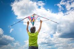 Um menino com um papagaio colorido em suas mãos contra o céu azul com nuvens Fotografia conceptual imagens de stock