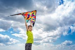 Um menino com um papagaio colorido em suas mãos contra o céu azul com nuvens Fotografia conceptual fotos de stock