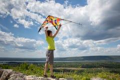 Um menino com um papagaio colorido em suas mãos contra o céu azul com nuvens Uma criança em um t-shirt amarelo e no short Bonito fotos de stock