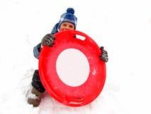 Um menino com trenó dos pires em uma neve no inverno imagem de stock royalty free