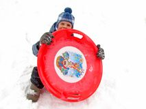 Um menino com trenó dos pires em uma neve no inverno foto de stock royalty free