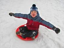 Um menino com trenó dos pires em uma neve no inverno, isolado no branco imagem de stock royalty free