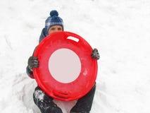 Um menino com trenó dos pires em uma neve no inverno, isolado no branco imagens de stock royalty free