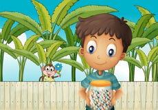 Um menino com um frasco dos doces que estão na frente da cerca com Imagem de Stock