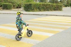 Um menino com uma bicicleta cruza um cruzamento pedestre com marcações amarelas Imagens de Stock