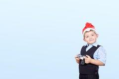 Um menino com uma câmera no chapéu de Santa Claus em um fundo claro Imagem de Stock