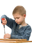 Um menino com uma chave de fenda Imagens de Stock Royalty Free
