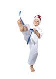 Um menino com uma correia azul e um tampão de Santa Claus bate um pé do pontapé Fotografia de Stock Royalty Free