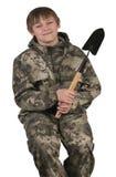 Um menino com uma ferramenta de jardim uma pá em um terno protetor Imagens de Stock