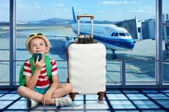Um menino com uma mala de viagem senta-se no aeroporto e espera-se a aterrissagem no plano fotos de stock