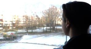 Um menino considerável um adolescente olha para fora a janela à rua foto de stock