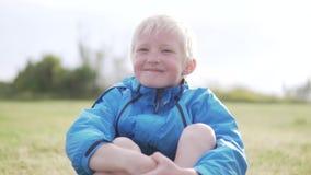 Um menino considerável do albino que senta-se em um parque na grama e no sorriso vídeos de arquivo