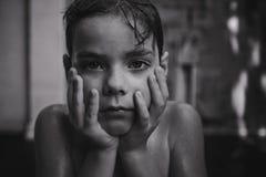 Um menino considerável pensativo com água deixa cair em sua cara Pequim, foto preto e branco de China fotos de stock