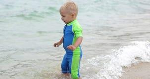 Um menino considerável vai ao mar