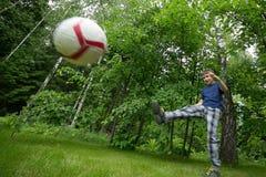 Um menino da aparência europeia joga o futebol Emoção brilhante, bola de voo imagens de stock royalty free