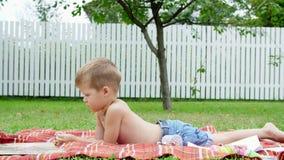 Um menino da criança de quatro anos lê um livro, no jardim, encontrando-se para baixo em uma cobertura, uma coberta, na grama, gr video estoque