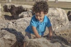 Um menino da criança está andando com cuidado através de algumas grandes rochas imagem de stock