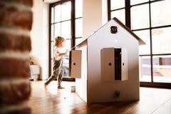 Um menino da crian?a que joga com uma casa do papel da caixa dentro em casa imagens de stock royalty free