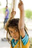 Um menino da vila que joga com um balanço Foto de Stock