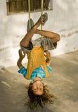 Um menino da vila que pendura upside-down Imagem de Stock Royalty Free