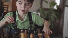 Um menino de 6 anos arranja figuras em uma placa de xadrez video estoque