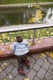 Um menino de dois anos em uma caminhada em um parque da cidade Fotografia de Stock Royalty Free