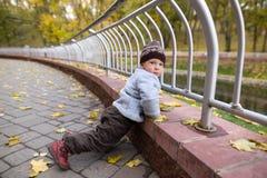 Um menino de dois anos em uma caminhada em um parque da cidade Fotografia de Stock