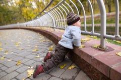 Um menino de dois anos em uma caminhada em um parque da cidade Fotos de Stock