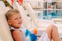 Um menino de sete anos caucasiano louro bonito est? encontrando-se pela associa??o exterior Cocktail de fruto alaranjado imagens de stock royalty free